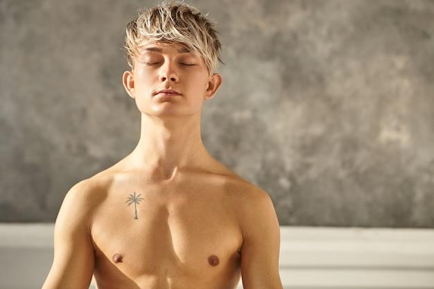 Портрет красивого татуированного мужчины, практикующего йогу в помещении, закрывая глаза во время медитации, имея мирный взгляд, концентрируясь на своем дыхании. молодой учитель-мужчина без рубашки делает медитацию в тренажерном зале Бесплатные Фотографии