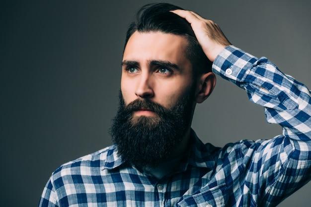 Портрет красивого думающего молодого человека, изолированного на серой стене Бесплатные Фотографии