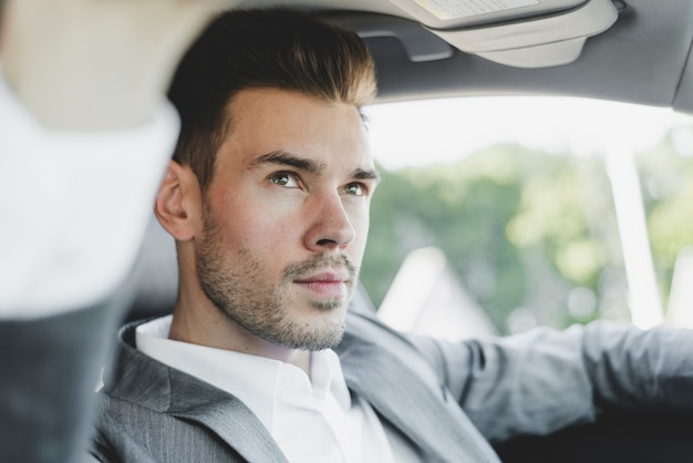 Portrait of handsome young businessman in the car Free Photo