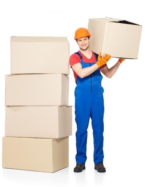 白い背景で隔離の紙箱とハンサムな若い配達人の肖像画 無料写真