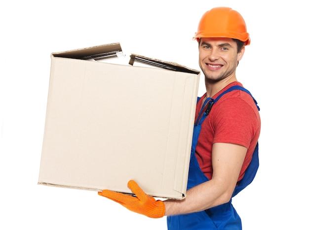 白い壁に分離された紙箱を持つハンサムな若い配達人の肖像画 無料写真