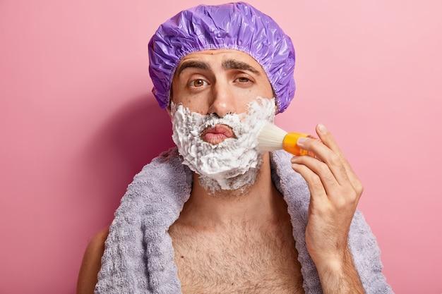 ハンサムな若いヨーロッパ人の肖像画は、ブラシで顔にシェービングフォームを適用し、ひげそりの準備をし、シャワーキャップを着用し、首に柔らかいタオルを持ち、屋内でトップレスに立っています。男性的なスキンケアのコンセプト 無料写真