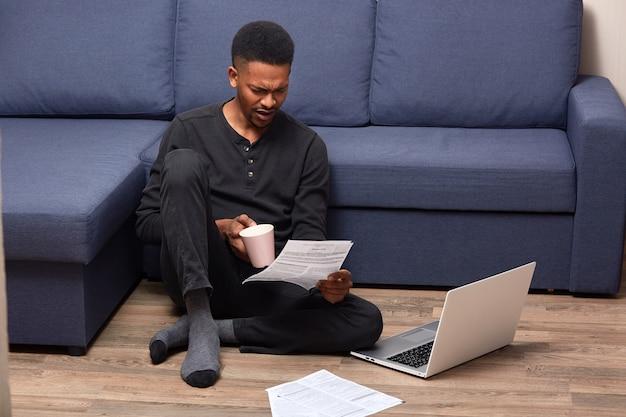 Портрет красивого молодого человека в черном повседневном наряде, сидящего на полу с ноутбуком, работающего с бумагами и пьющего кофе Premium Фотографии