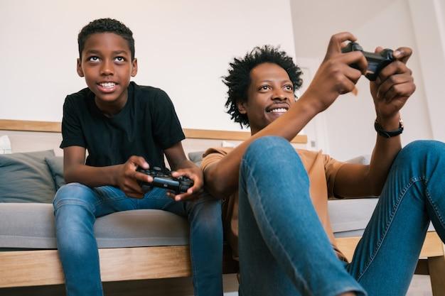 幸せなアフリカ系アメリカ人の父と息子のソファーソファに座って、家で一緒にコンソールビデオゲームをプレイの肖像画。家族と技術の概念。 無料写真