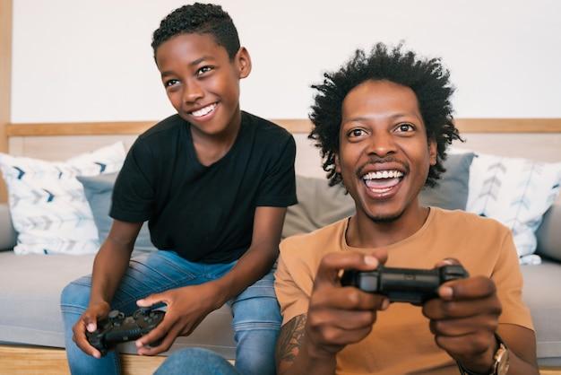행복 한 아프리카 계 미국인 아버지와 아들 소파 소파에 앉아 집에서 콘솔 비디오 게임을 함께하는 초상화. 가족 및 기술 개념. 무료 사진