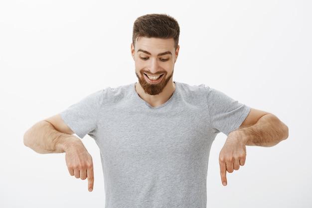 Портрет счастливого и изумленного красивого мужского пола с идеальной прической и бородой, смотрящего вниз с восторгом и любопытством, наслаждающегося наблюдением вниз в интересном пространстве для копирования. Бесплатные Фотографии