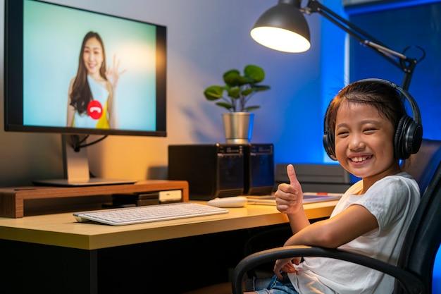 自宅で先生とオンラインで勉強するためにビデオ電話会議を使用して幸せなアジアの女の子の肖像画。遠隔教育、オンライン学習、テクノロジー、またはリモート接続の概念 Premium写真