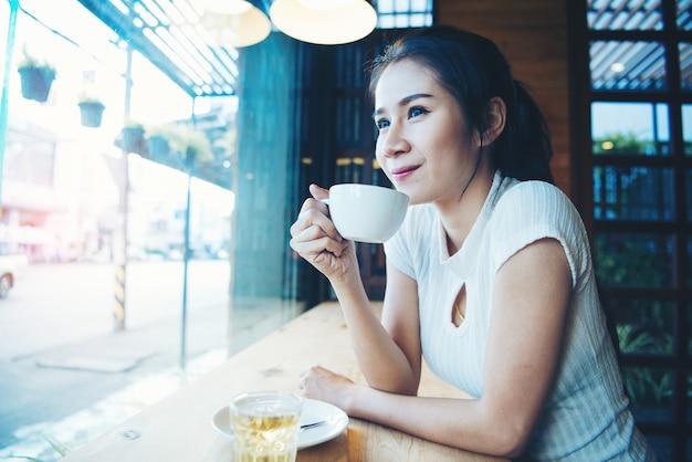 手でマグカップと幸せな美しい女性の肖像画 無料写真