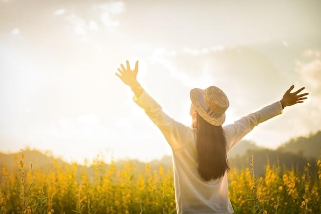 Портрет счастливый счастливый молодой женщины, расслабляющий в парке. радостная женская модель, дышащая свежим воздухом на открытом воздухе и наслаждающаяся запахом в цветочной весне или летнем саду, старинный тон Premium Фотографии