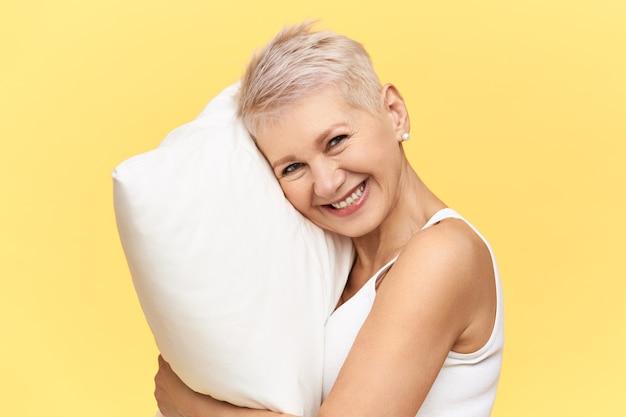 편안한 메모리 폼 흰색 베개에 전체 밤 수면 때문에 활기찬 표정을 갖는 셔츠 머리를 가진 행복 아름다운 중년 여성의 초상화. 무료 사진