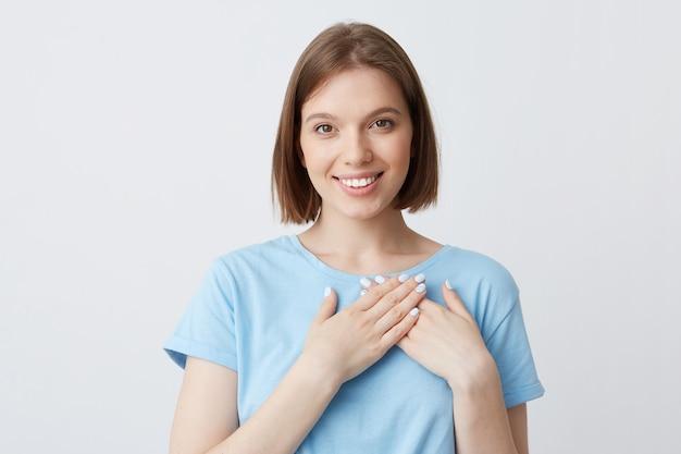幸せな美しい若い女性の肖像画は彼女の心の領域に手を保つ青いtシャツを着ています。 無料写真
