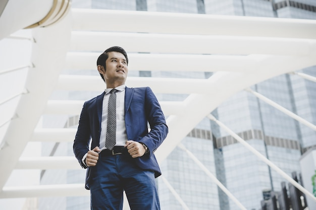 Portrait of happy businessman standing on front of business center. Free Photo