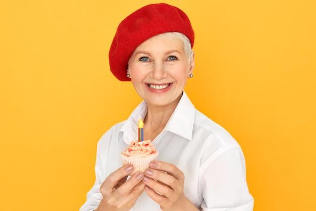 행복 한 매력적인 중간 나이 든된 백인 여성의 초상화 그녀의 생일을 축 하하는 세련 된 빨간 모자에 그녀의 손에 컵 케 잌은 절연 포즈. 축하, 파티 및 특별 행사 개념 무료 사진