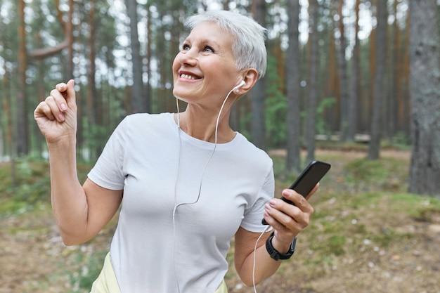 白いtシャツと屋外で楽しんでいるイヤホンで幸せな陽気な成熟した女性の肖像画 無料写真