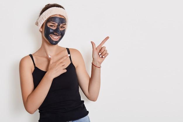 幸せな陽気な女性の肖像画は、彼女の顔の皮膚を改善し、ピーリングマスクを適用し、元気で、白い壁にポーズをとって両手を脇に向けるモデルです。 無料写真
