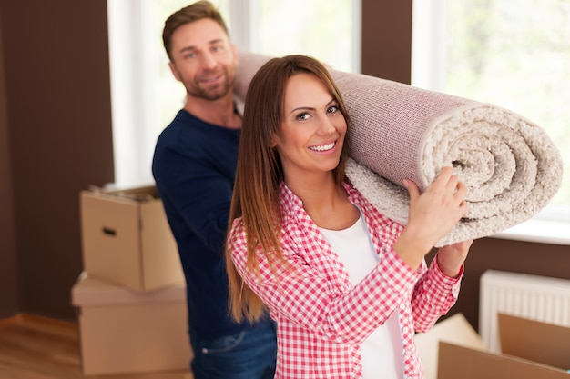 新しい家のためにカーペットを運ぶ幸せなカップルの肖像画 無料写真