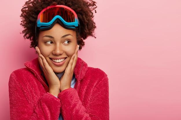 행복 한 곱슬 머리 소녀 Snowboader의 초상화는 적극적인 휴식을 즐기고, 뺨을 부드럽게 만지고, 이빨 미소로 멀리 보이며, 분홍색 배경에 고립 된 빨간 코트, 스키 안경을 착용합니다. 무료 사진