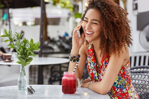 Портрет счастливой темнокожей женщины с темной кожей искренне смеется, пока общается с другом по смартфону, проводит свободное время в кафе. Бесплатные Фотографии