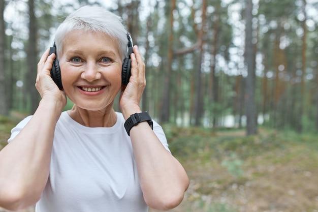 ヘッドフォンで手をつないで、屋外でジョギングしながら音楽を聴いて幸せでエネルギッシュな中年女性の肖像画 無料写真