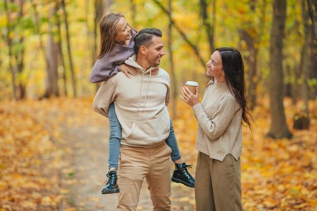 Портрет счастливой семьи из трех человек в осенний день Premium Фотографии