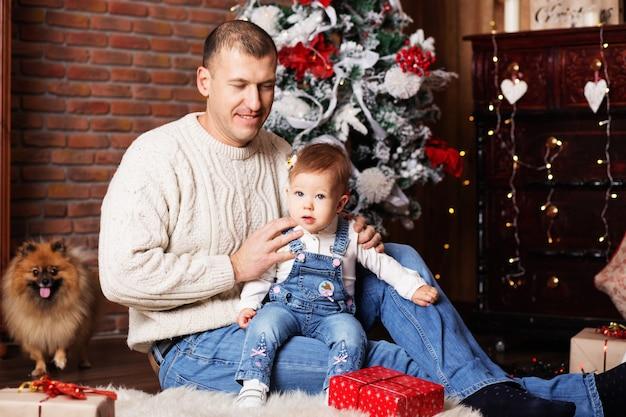Портрет счастливого отца и его очаровательной маленькой дочери среди рождественских украшений Premium Фотографии