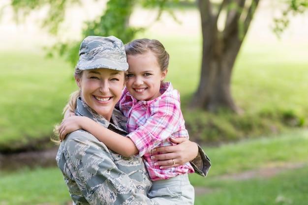 公園で彼女の娘と一緒に幸せな女性兵士の肖像画 Premium写真