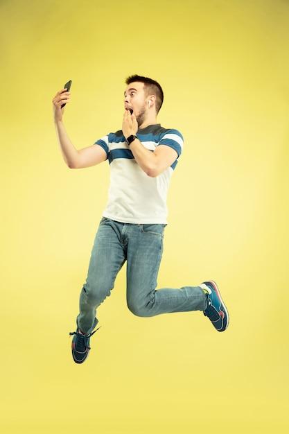 노란색 벽에 가제트와 함께 행복 점프 남자의 초상화 무료 사진