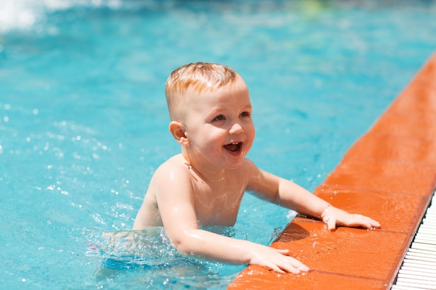 Portrait Of Happy Little Boy Swimming In Pool