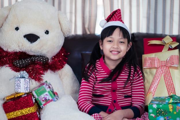 クリスマスプレゼントとクリスマス帽子の上の幸せな少女の肖像画 Premium写真