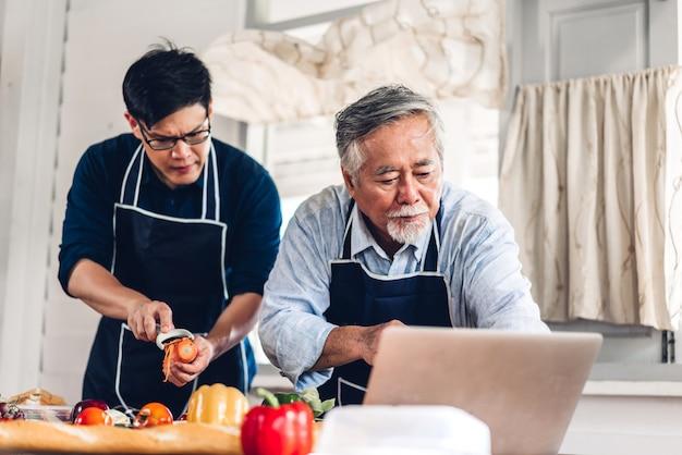 幸せな愛アジア家族シニア成熟した父と一緒に料理を楽しんで、ラップトップコンピューターでインターネット上のレシピを探している若い大人の息子の肖像画 Premium写真