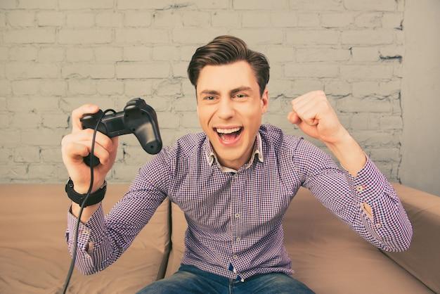 Портрет счастливого человека, выигрывающего видеоигру, держащего джойстик Premium Фотографии