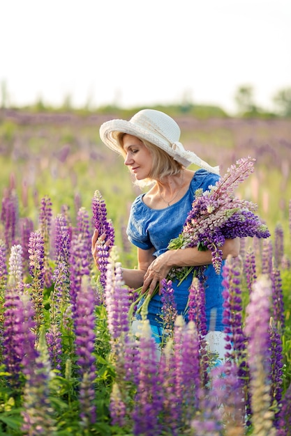 開花ルピナスフィールドの帽子で幸せな中年女性の肖像画。女性の幸福の概念。 Premium写真
