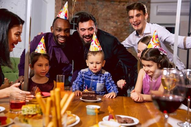 自宅で誕生日を祝う幸せな多民族家族の肖像画。大家族がケーキを食べたり、ワインを飲んだりしながら、子供たちに挨拶したり楽しんだりしています。お祝い、家族、パーティー、家のコンセプト。 無料写真