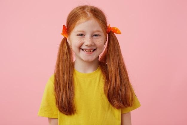 Портрет счастливой миниатюрной рыжеволосой девушки с веснушками с двумя хвостами, широко улыбаясь и мило выглядит, носит желтую футболку, стоит на розовом фоне. Бесплатные Фотографии