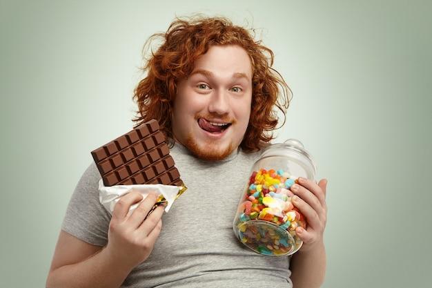 陽気な表情でカメラを見て幸せな肉付きの良い若い赤毛のひげを生やした男の肖像 無料写真