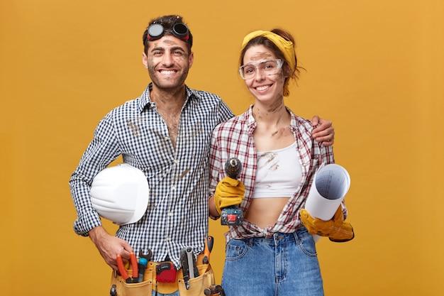 Портрет счастливых сотрудников по техническому обслуживанию, работающих вместе: веселый мужчина в ремне с инструментами, обнимающий симпатичную женщину с дрелью и планом, стоящих рядом друг с другом Бесплатные Фотографии