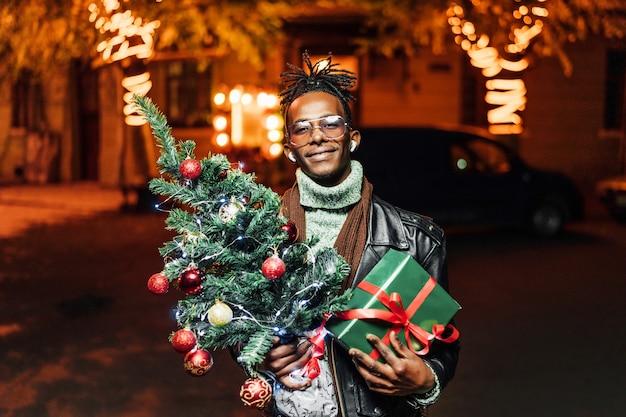 Портрет счастливого довольного афроамериканца, стоящего с елкой и подарком в руках и улыбающегося Premium Фотографии