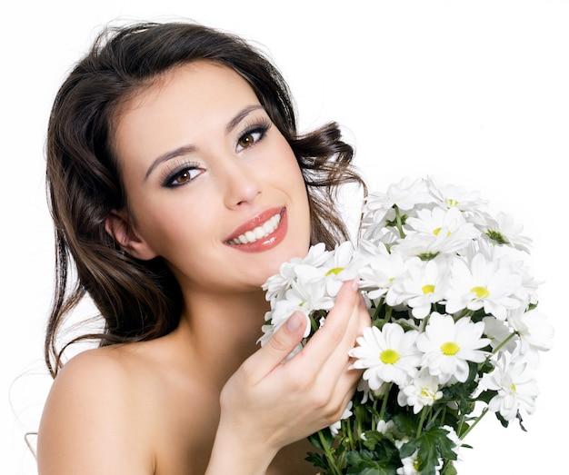 꽃다발 꽃과 함께 행복 한 미소 아름 다운 젊은 여자의 초상화-흰색에 고립 무료 사진