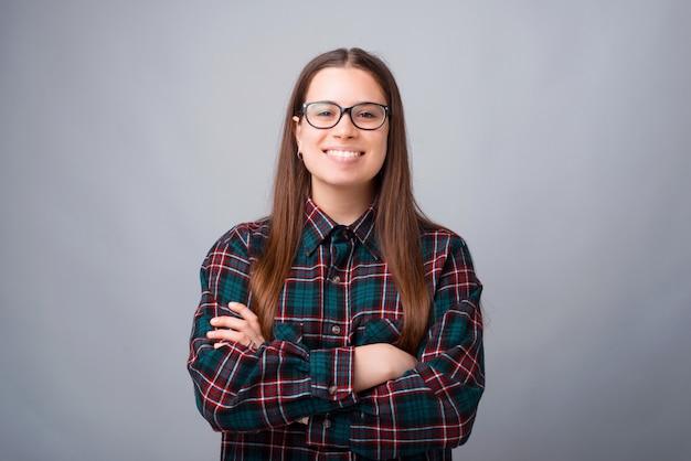 Портрет счастливой улыбающейся женщины со скрещенными руками, уверенно смотрящей в камеру Premium Фотографии