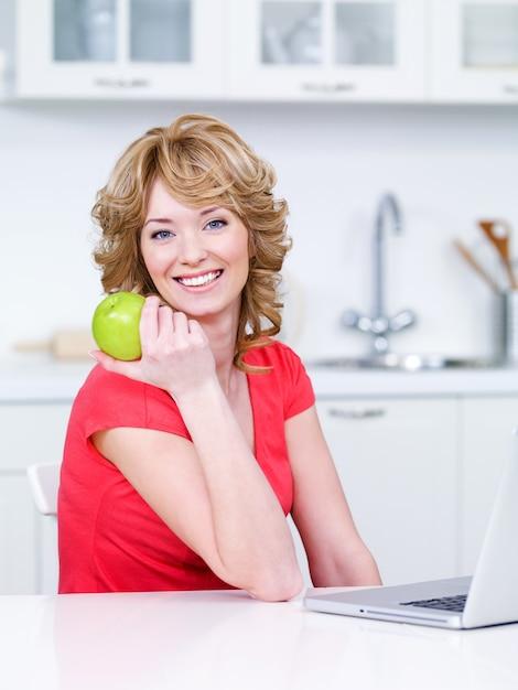 Портрет счастливой улыбающейся женщины с зеленым яблоком, сидящей на кухне Бесплатные Фотографии