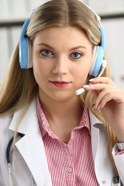 ヘッドセットで幸せな笑顔の若い医者の肖像画 Premium写真