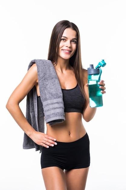 Портрет счастливой улыбкой молодой женщины в фитнесе носить с бутылкой воды, изолированных на белом Бесплатные Фотографии