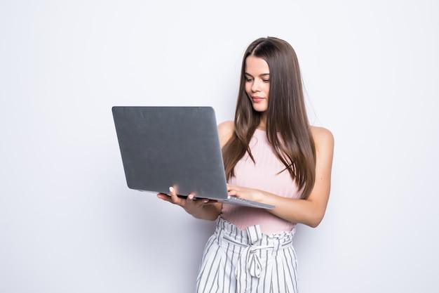 Портрет счастливой удивленной женщины, стоящей с ноутбуком, изолированным на серой стене. Бесплатные Фотографии