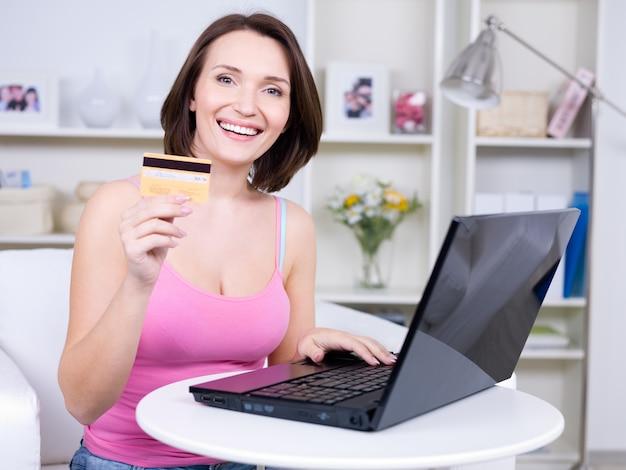 Портрет счастливой молодой красивой женщины, держащей кредитную карту и использующей ноутбук Бесплатные Фотографии