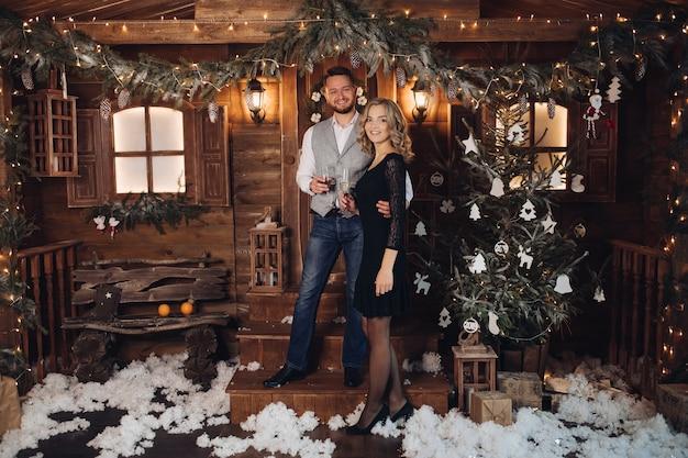 Портрет счастливой молодой пары в элегантных нарядах, улыбающейся лицом к лицу с двумя бокалами шампанского Бесплатные Фотографии