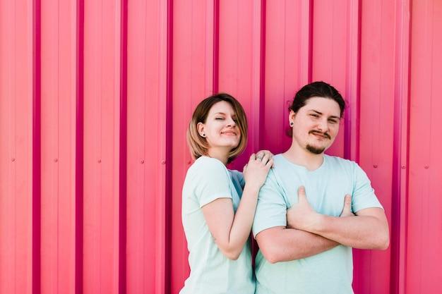 Портрет счастливой молодой пары стоял против розового гофрированного металлического листа Бесплатные Фотографии