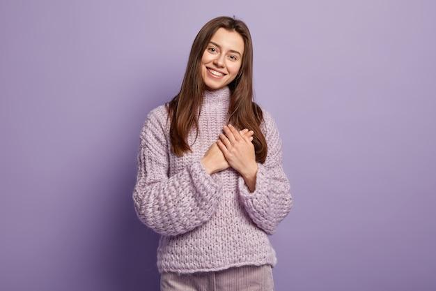 幸せな若いヨーロッパの女性の肖像画は、胸に手を保ち、心のジェスチャーを示し、感謝の気持ちを表し、感謝し、紫色の壁のボディーランゲージに対するモデルです。モノクロ。人と献身 無料写真