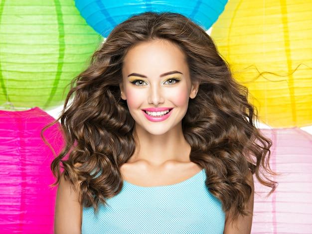 長い茶色の髪の幸せな少女の肖像画。白い背景の上の白人のかなり笑顔の女性のクローズアップの顔 無料写真
