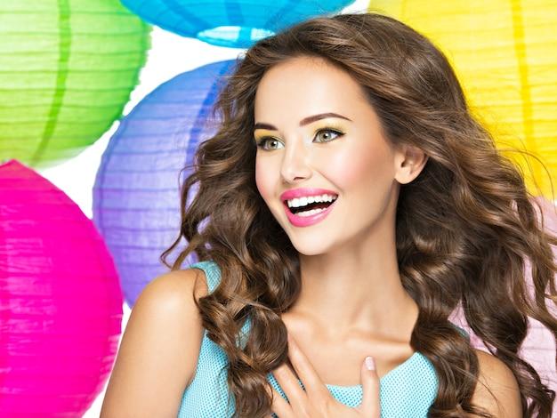 긴 갈색 머리를 가진 행복 한 젊은 여자의 초상화. 흰색 배경 위에 백인 꽤 웃는 여자의 근접 촬영 얼굴 무료 사진
