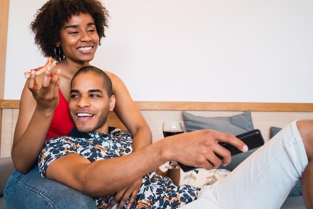Портрет счастливой молодой латинской пары, проводящей время вместе и смотрящей телевизор в их доме. концепция образа жизни и отношений. Premium Фотографии